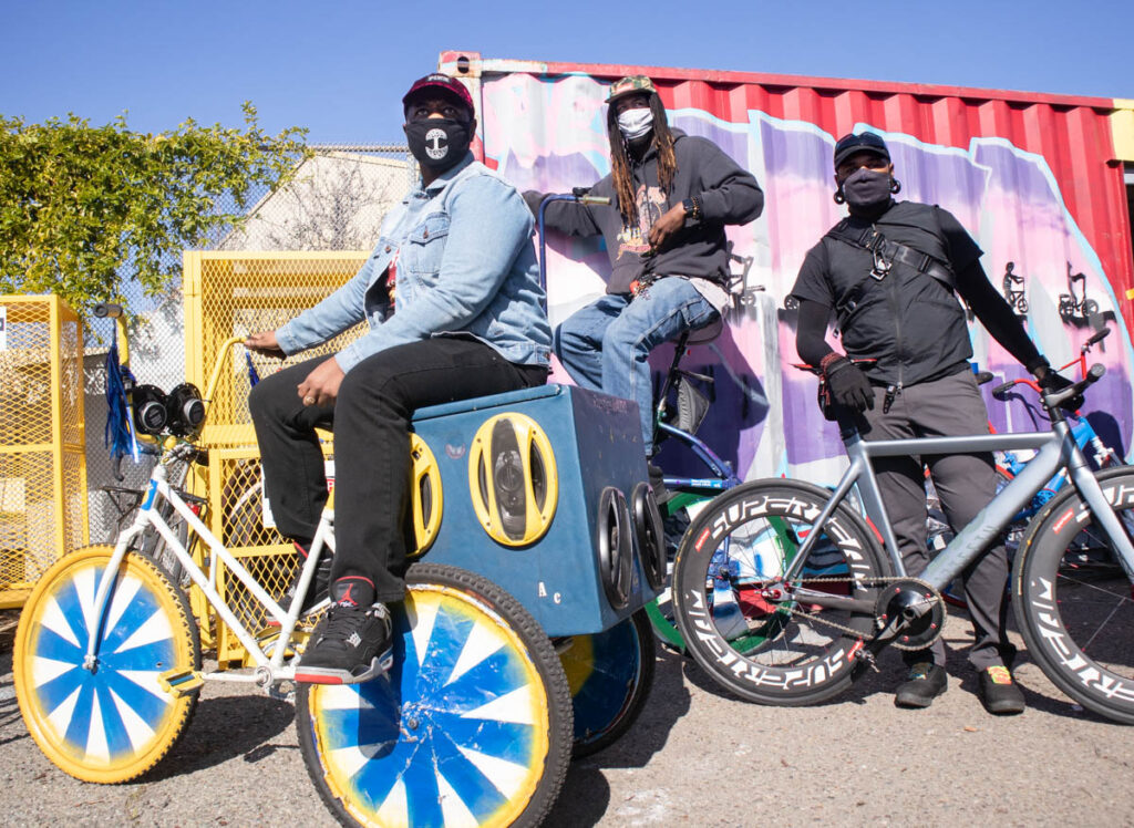 Three men on sitting on colorfully decorated bikes in front of a colorfully painted shipping container